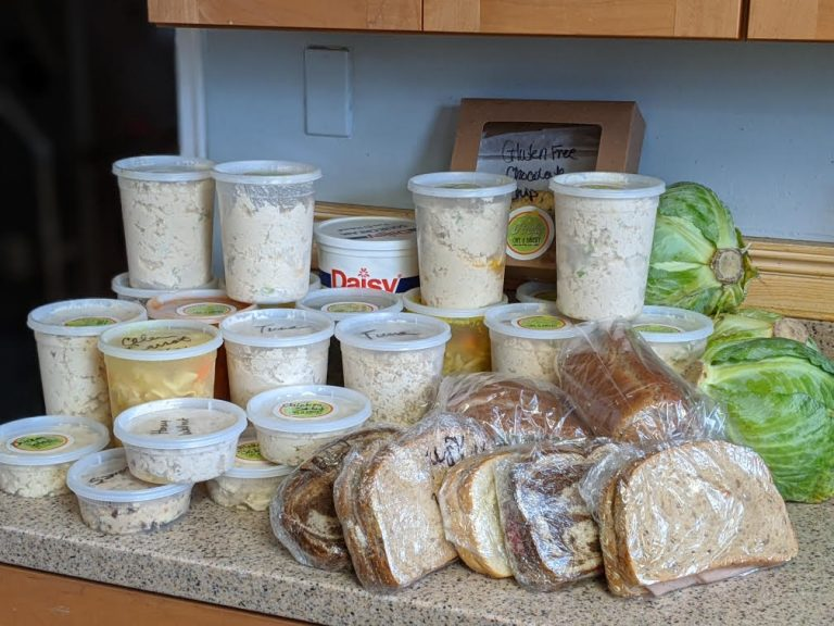 Image of sandwiches, vegetables, and plastic containers full of soup and chicken salad sitting on a counter top.